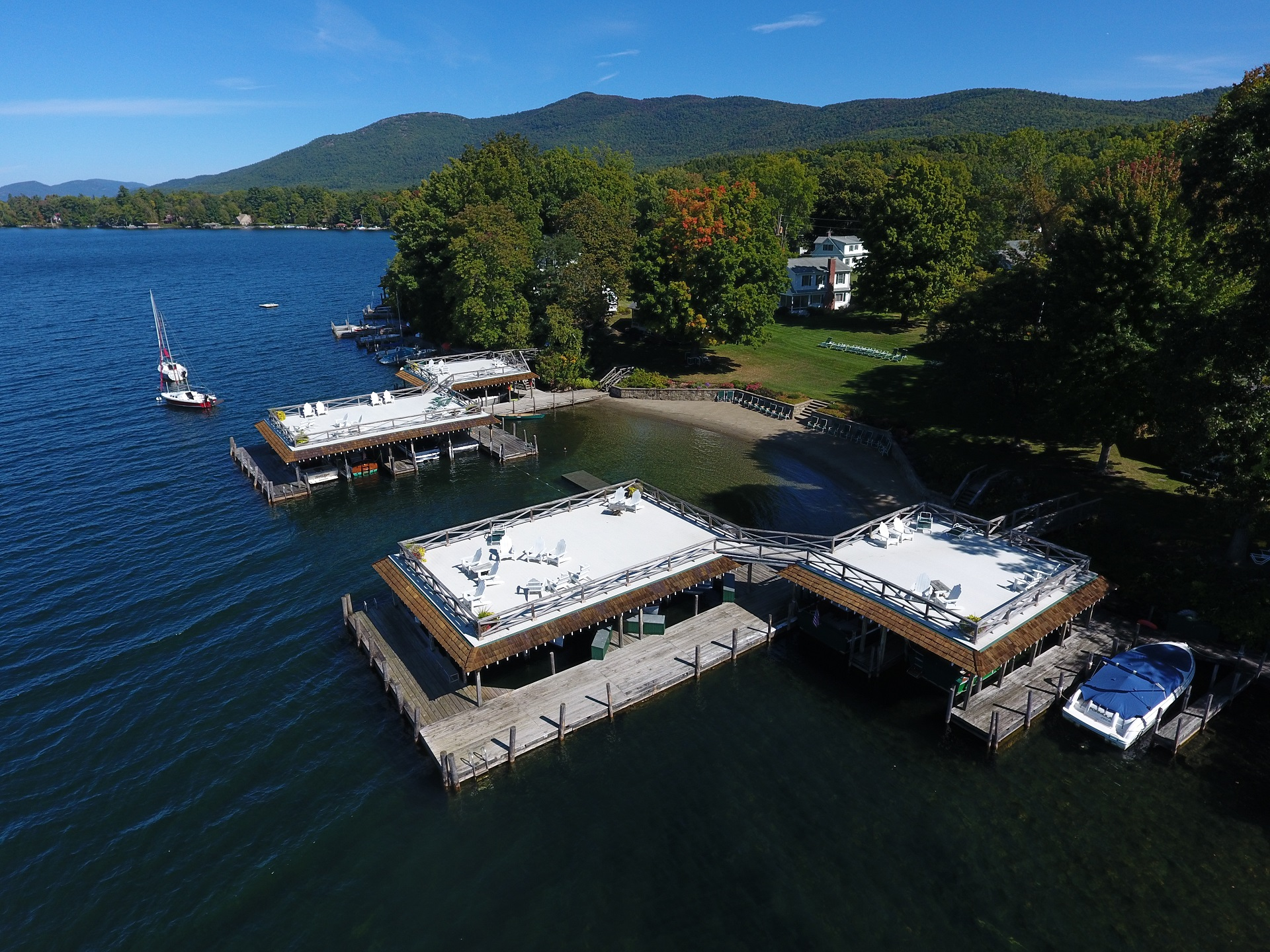 Lake George vacation cabin rentals boathouse sundecks and beach with fall foliage at Takundewide Cottages on Lake George