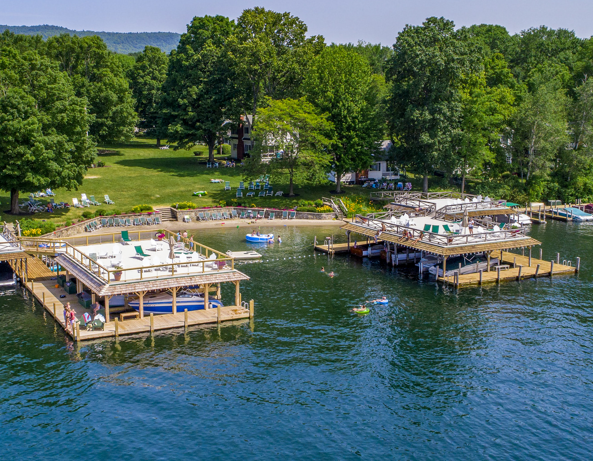 Lake George vacation cabin rentals beach, protected swimming area, and boathouse sundecks at Takundewide Cottages